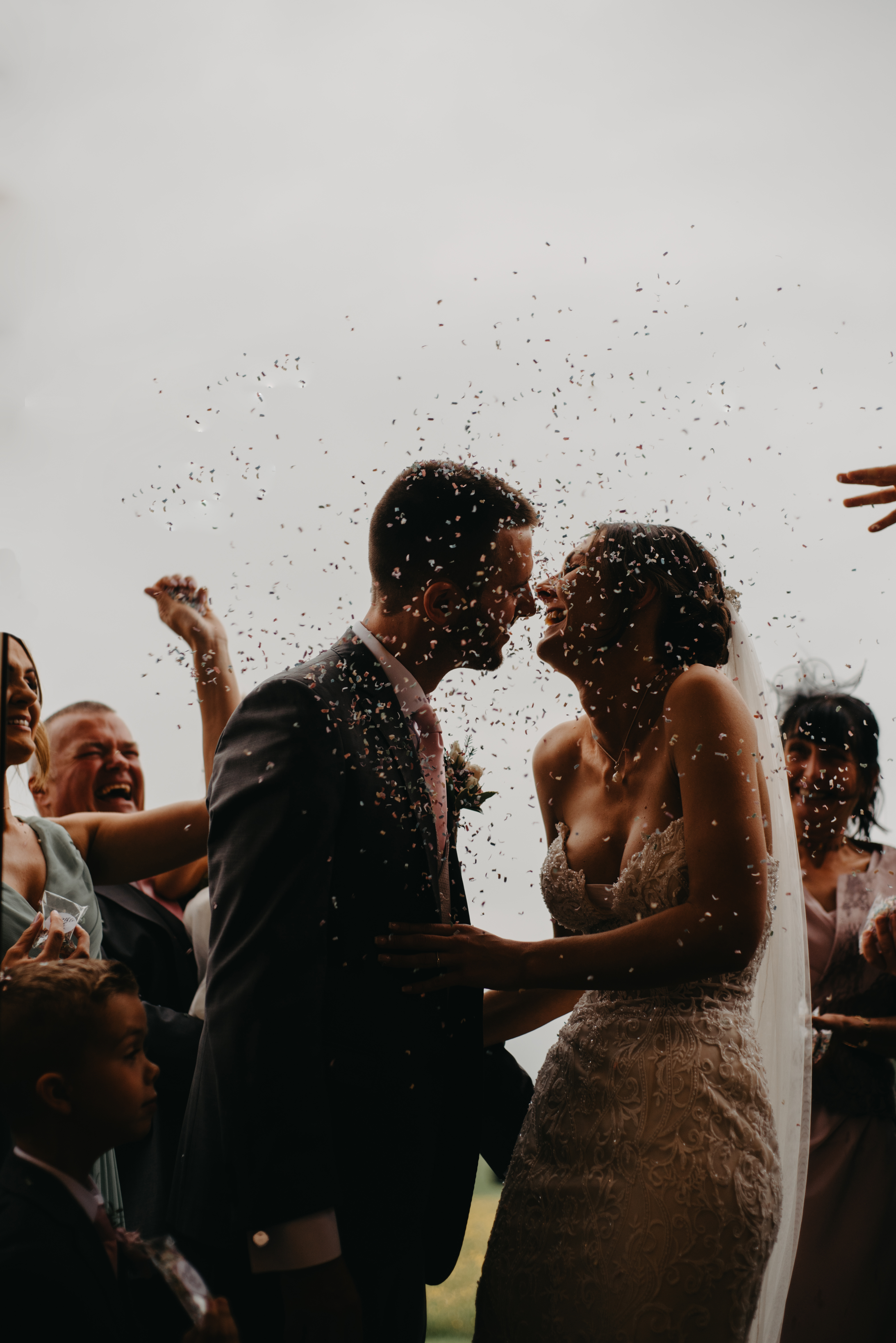 A bridal couples laughs as guests throw confetti on them