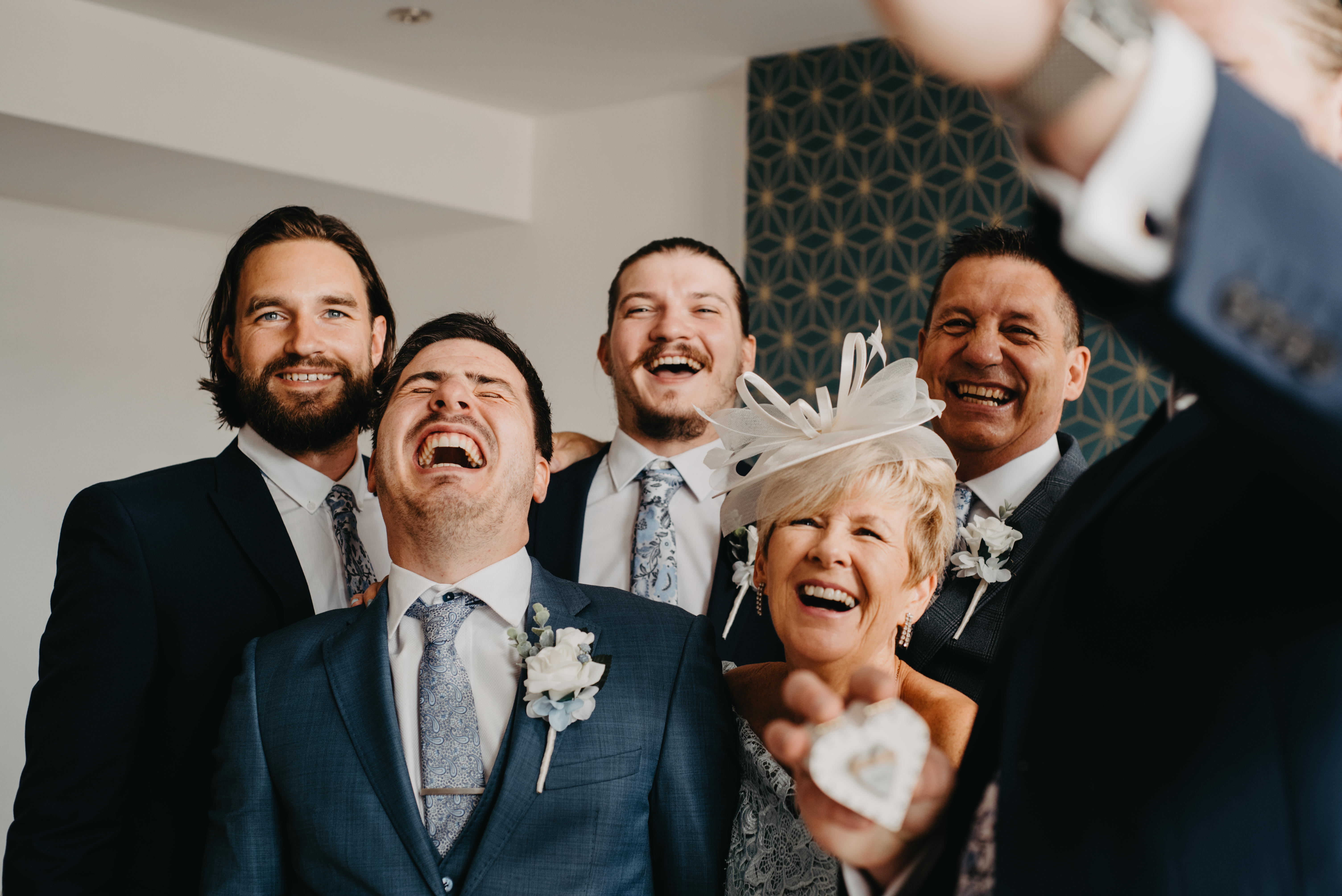 A groom and his groomsmen taking a selfie and laughing