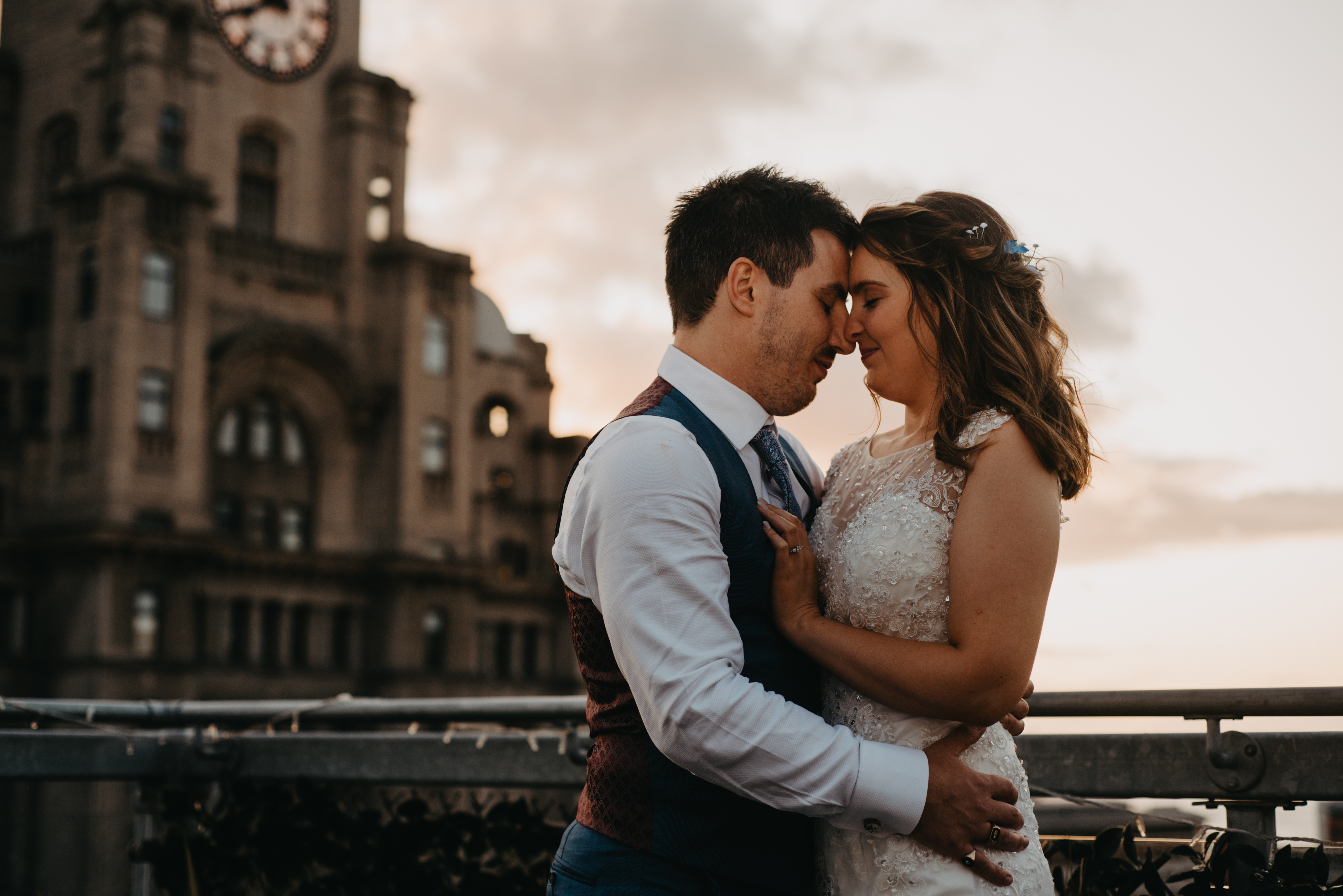 Bride and groom cuddles with heads pressed together on a rooftop in Liverpool