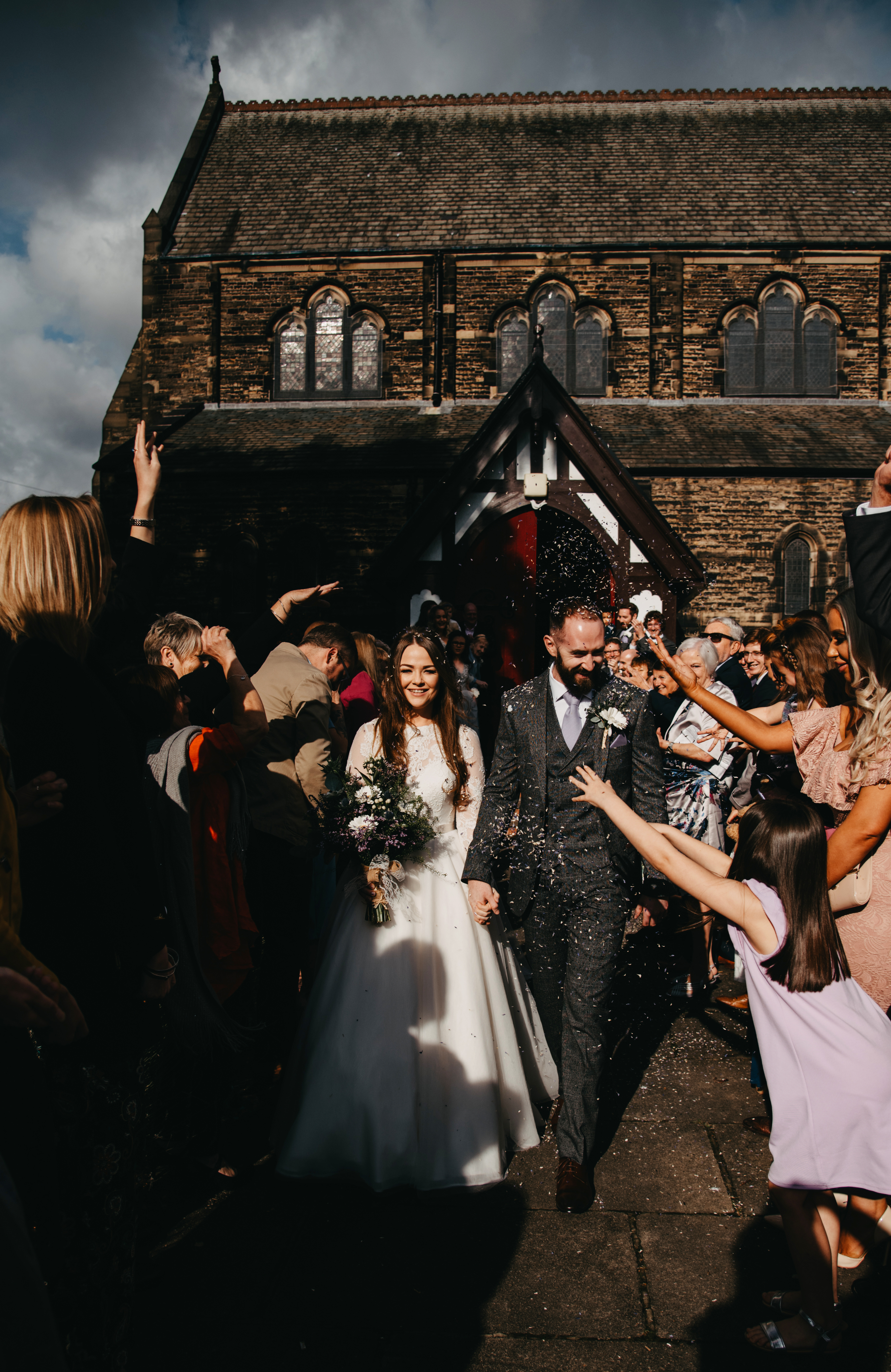 A bride and grooms walks as guests throw confetti over them