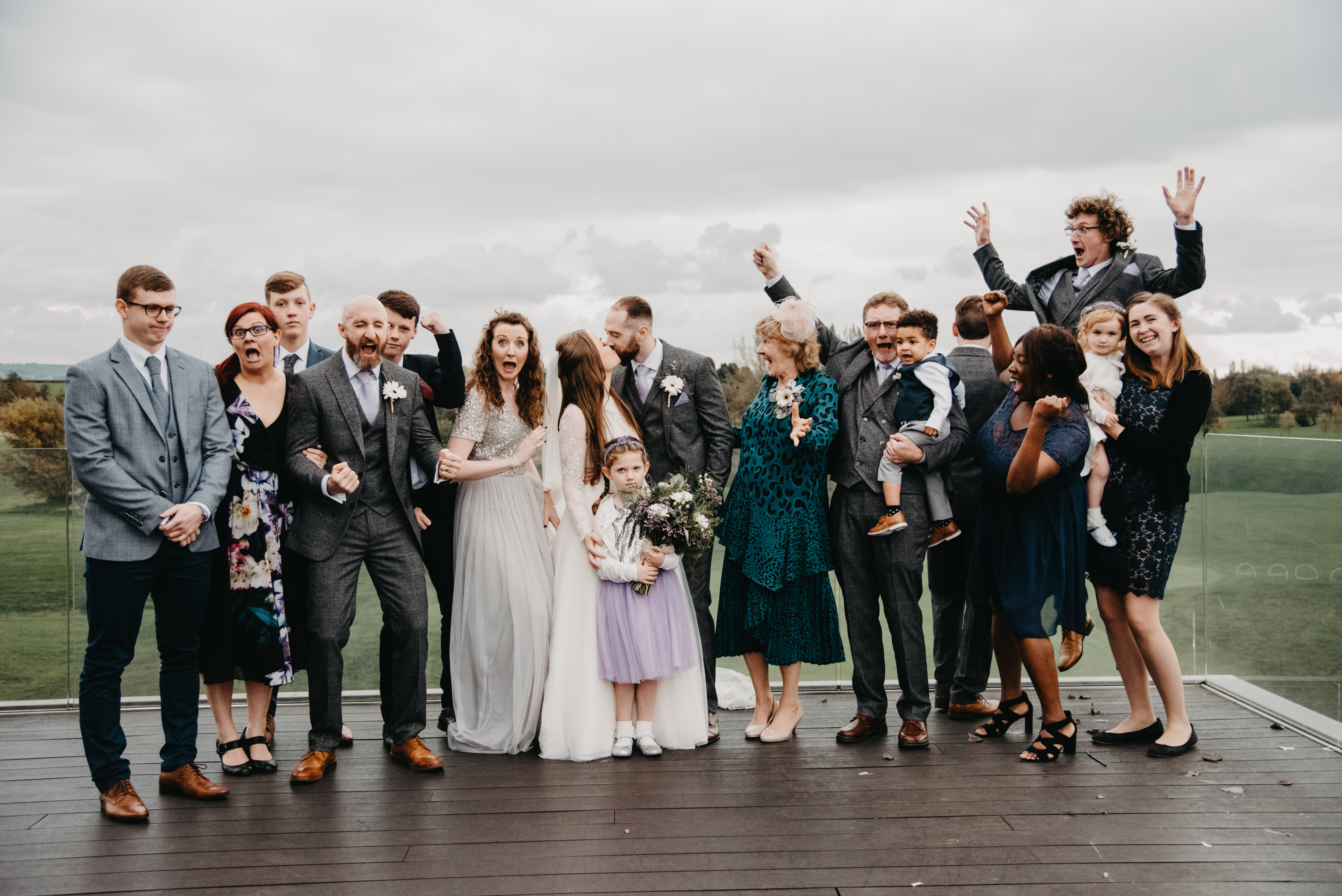 A bride and groom kisses while their family act silly