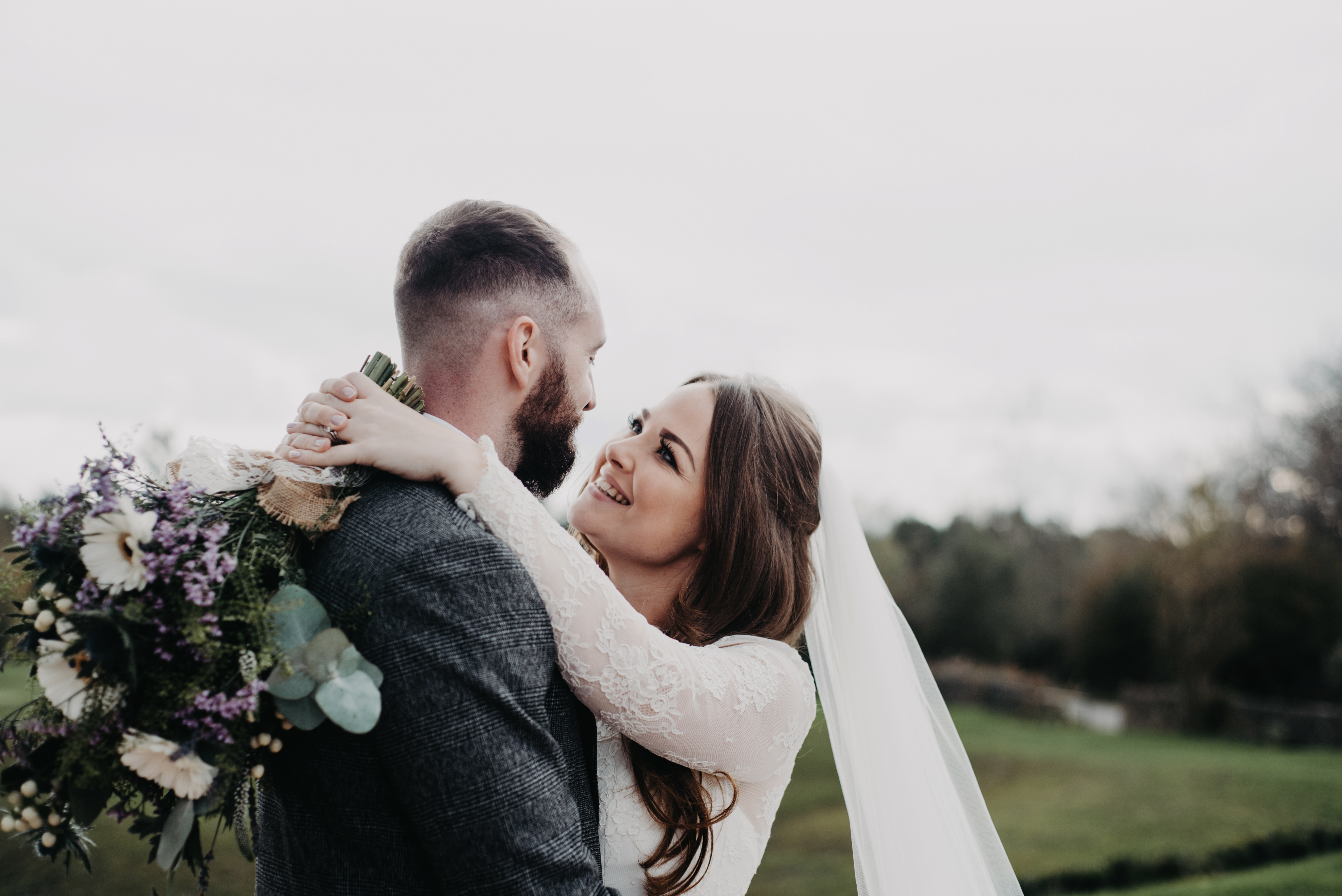 A bride and groom looks into eachothers eyes and smiles
